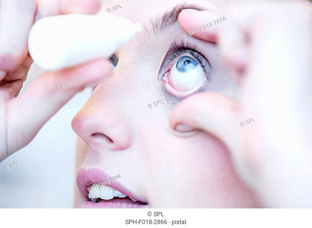 Close-up of person applying eye drops