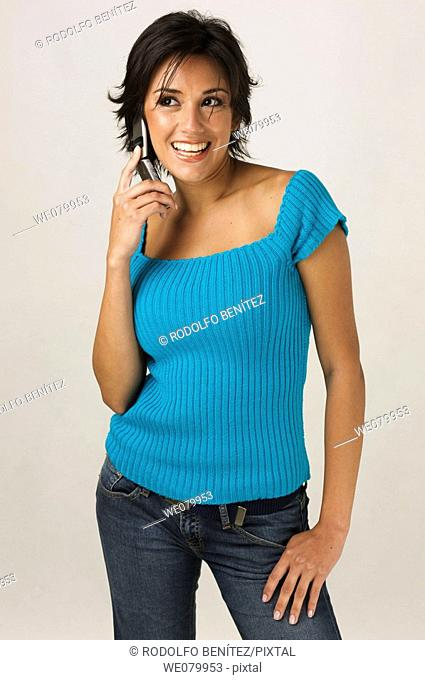 Young Latin model in her 20s talking on a cell phone smiling