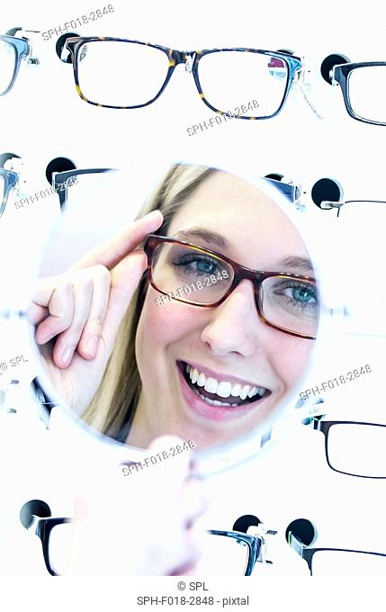 Woman trying on glasses in optometrist's shop in front of mirror