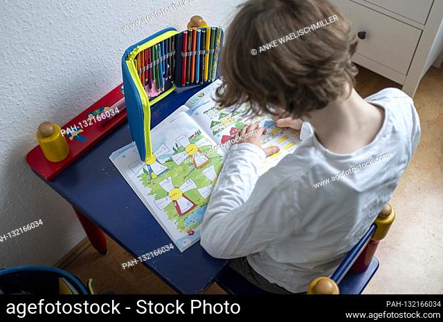 """Erstklaessler (7 years old) is sitting at a table at home doing maths in his booklet """"""""Arithmetic up to 20"""""""" on May 4th, 2020 in Muelheim an der Ruhr / Germany"""