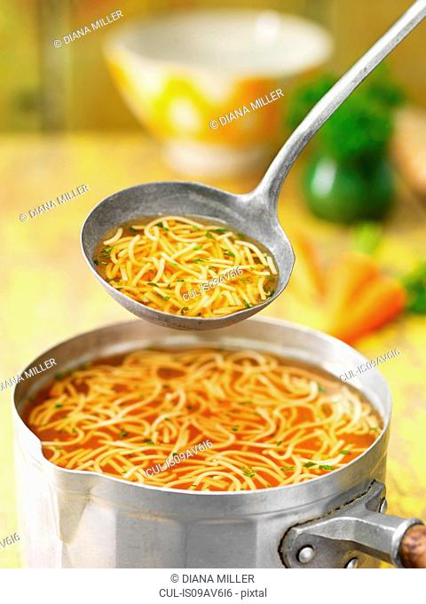 Saucepan and ladle of beef noodle soup with carrots, herbs and stock