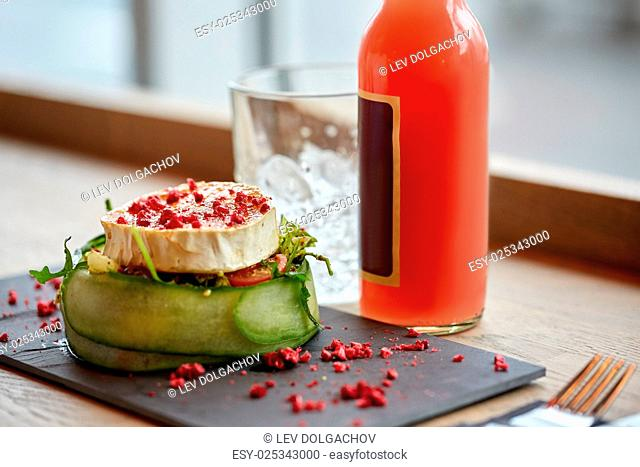 food, eating and object concept - goat cheese salad with vegetables, bottle of drink, glass with ice at restaurant or cafe