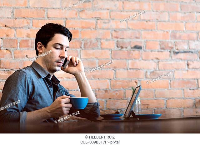 Man using mobile phone at cafe