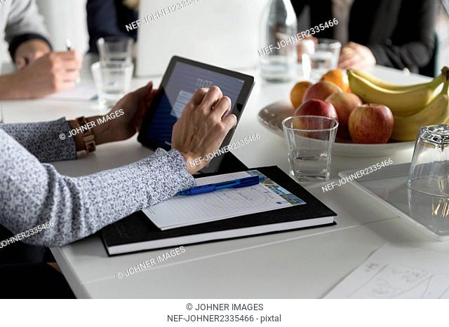 Woman using digital tablet at business meeting