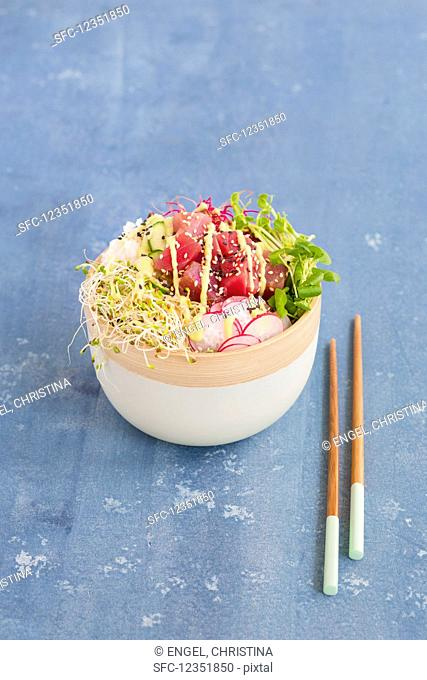 A Poke bowl with tuna, sushi rice, radishes, cucumber slices, and sprouts