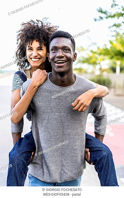 Young man carrying his girlfriend piggyback in the street