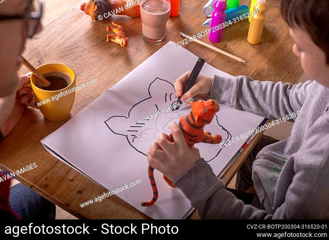 Boy drawing with his father