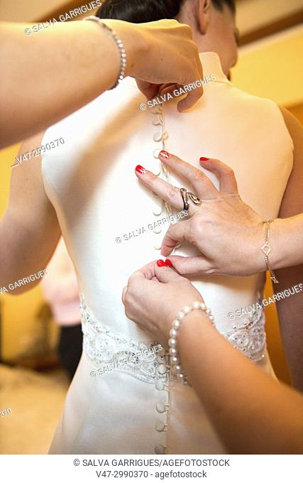Close-up of the hands of friends and family helping to take the buttons of the suit to the bride