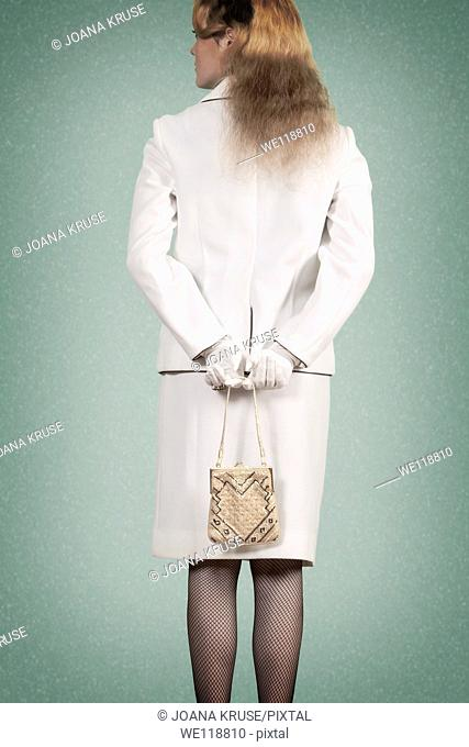 a woman in a vintage skirt suit is holding a handbag