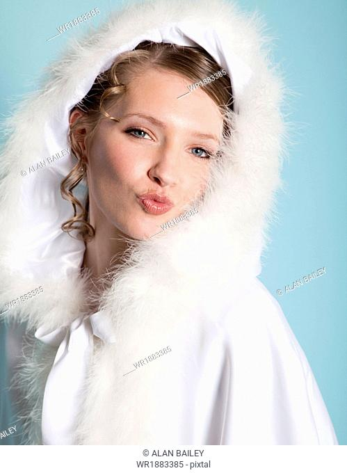 Portrait of happy bride wearing fur hood and puckering lips