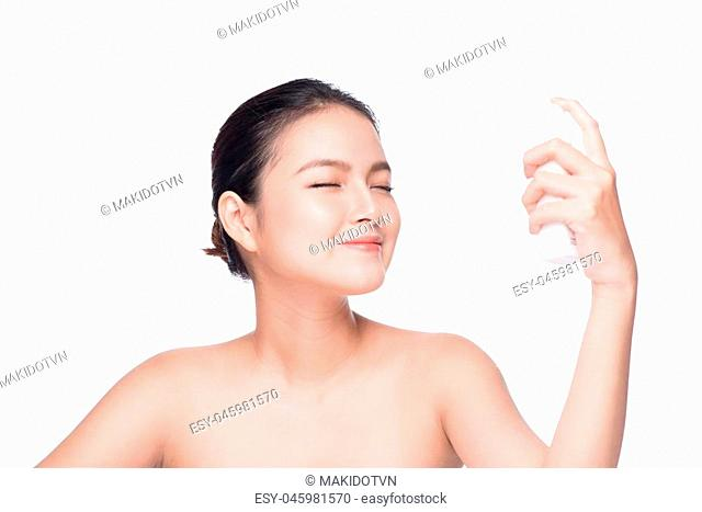 Beautiful asian woman applying spray water on face isolated white background