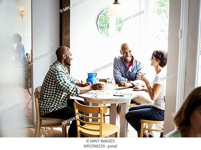 Two men and a woman sitting at a table in a cafe, having lunch