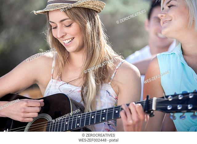 Happy friends with guitar outdoors