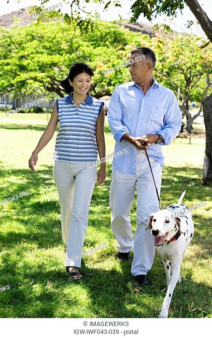 A couple walking with dog in park
