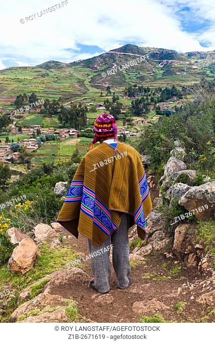 Peruvian farmer looking out over the fields above the village of Misminay, Peru