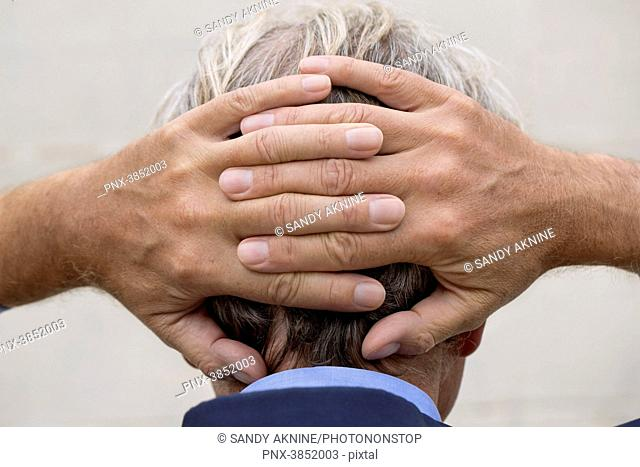 Close-up of man's hands in suit with fingers crossed behind the head