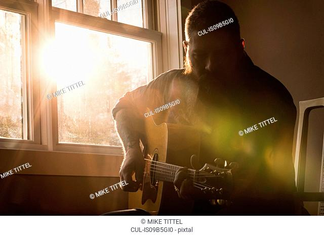 Man playing guitar beside window