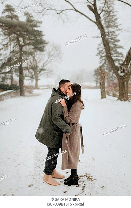 Couple hugging in snowy landscape, Georgetown, Canada