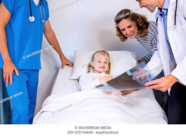 Doctors showing x-ray to patient and mother