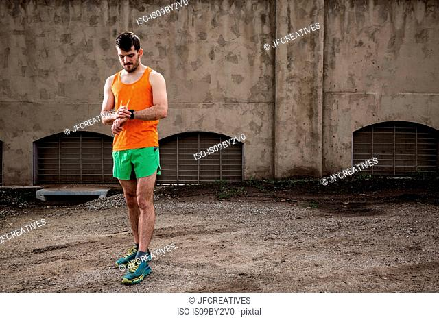 Young male runner checking smartwatch in front of urban wall
