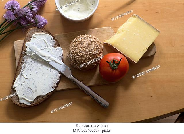 Cheese spreading on slice of brown bread in the kitchen