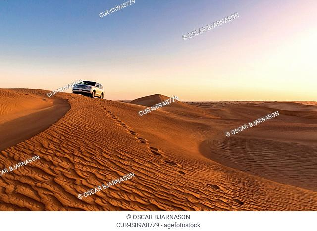 Footprints leading from car in desert, Dubai, United Arab Emirates