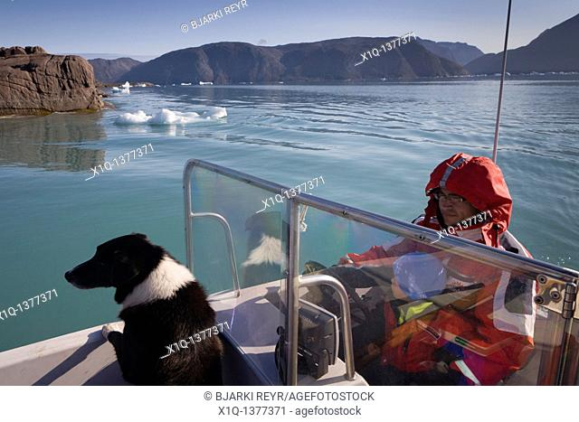 Man on his boat with his son and dog, South Greenland