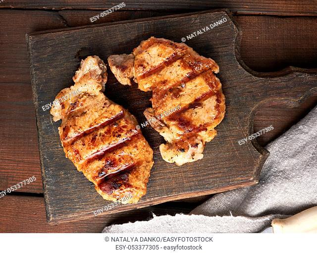 pork fried steak lies on a vintage brown wooden board, top view