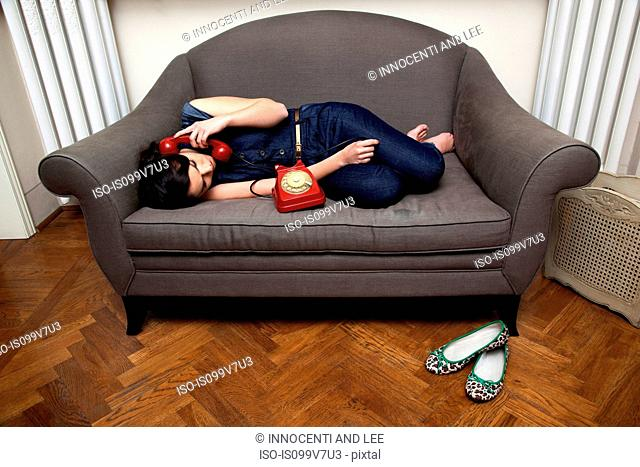 Woman lying on sofa on the telephone