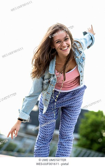 Portrait of smiling teenage girl balancing with outstretched arms