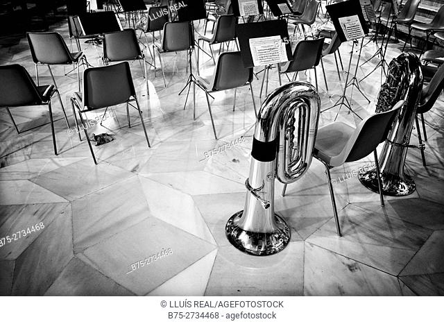 Concert hall with empty chairs, music scores and two tubas on the floor