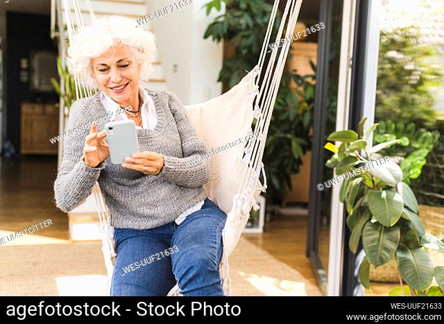 Mature woman using smart phone sitting on swing at home