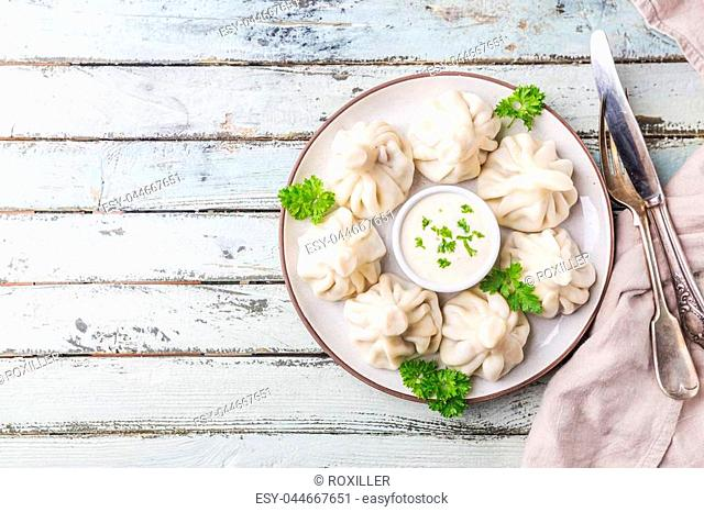 Georgian dumplings Khinkali with meat, greens and sauce on white plate, top view