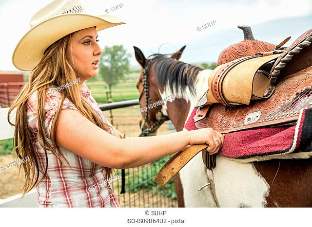Young woman on farm, saddling horse