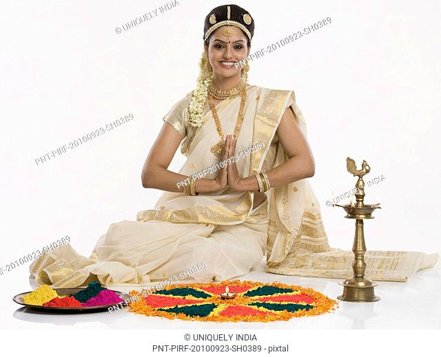 Indian woman in traditional clothing praying at Durga puja festival