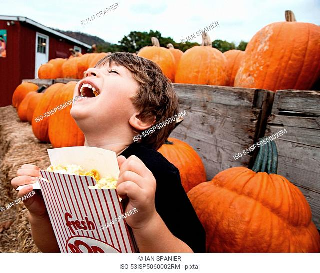 Boy eating popcorn in pumpkin patch