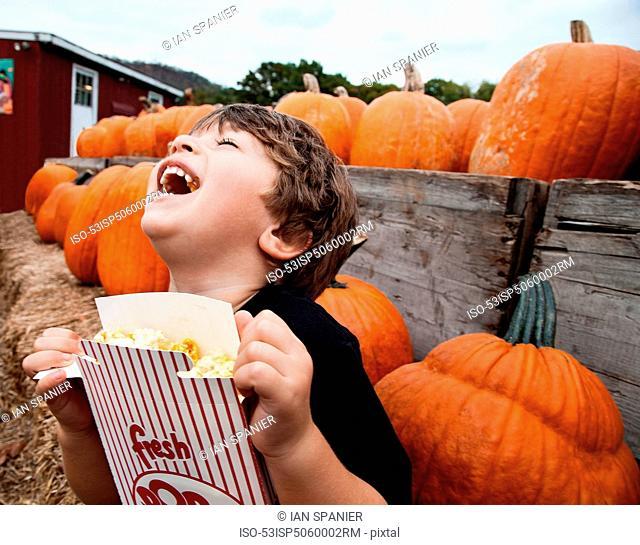 Boy eating popcorn in pumpkin patch