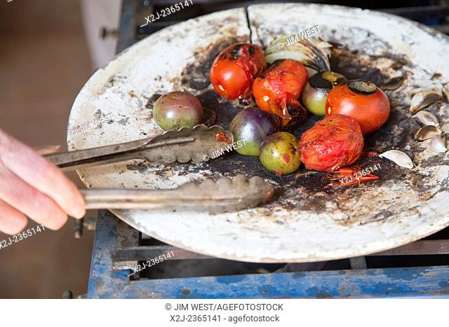 Oaxaca, Mexico - Vegetables used in making mole negro roasting on a comal during a cooking class