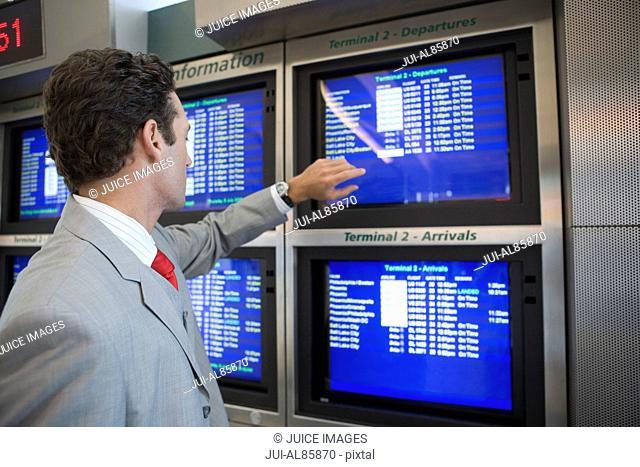 Businessman looking at Arrivals screen