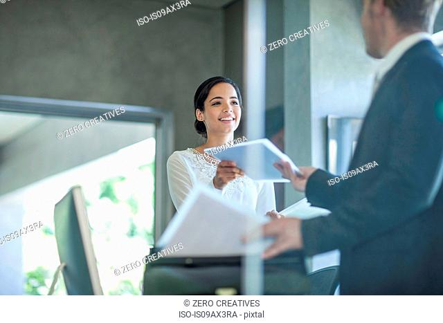 Office worker handing paperwork to businessman at office desk