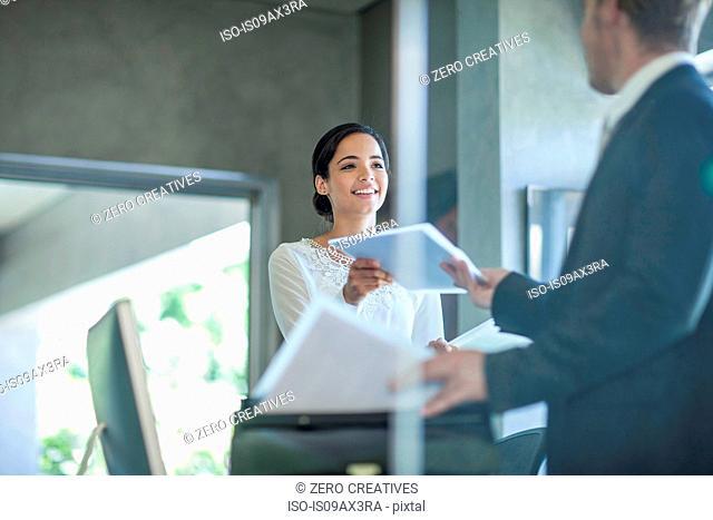 Office worker handing paperwork to businessman at office desk
