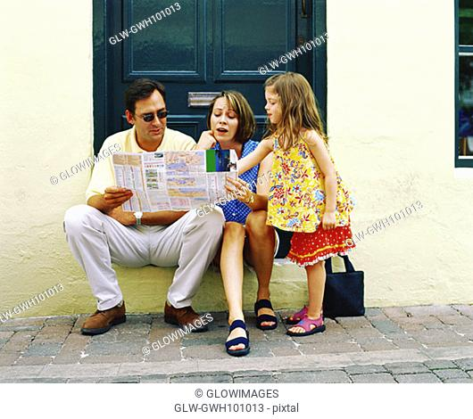 Young couple reading a newspaper with their daughter standing near them, Bermuda