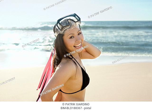 Asian woman wearing goggles at beach
