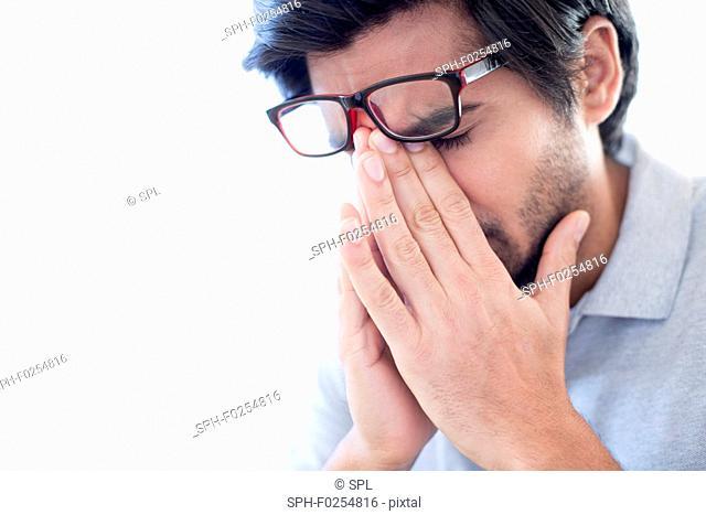Man pinching the bridge of his nose, wearing glasses