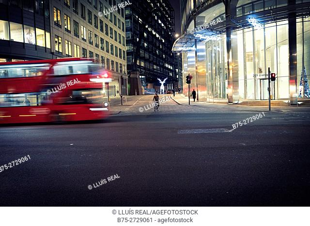 Night street scene: office buildings, bus in motion, bicyclist and pedestrians. Bishopsgate, London, England