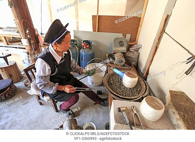 Bai woman making a silver pot. Heqing is famous for the production of Silverware- Yunnan, China