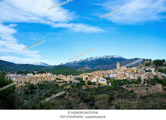 Mediterranean village surrounded by snow caped mountains