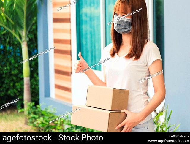 Asian delivery express courier young man giving parcel boxes to woman customer receiving both protective face mask and show thumbs up finger for good support...