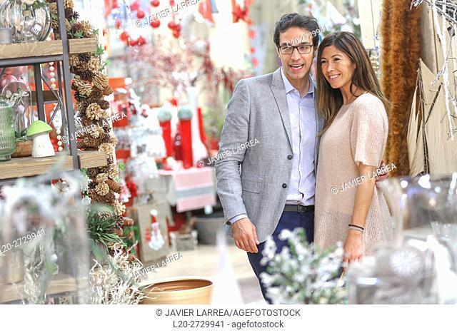Couple buying Christmas ornaments, garden center