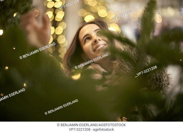 portrait of playful young woman grabbing lights of Christmas tree, in city Munich, Germany
